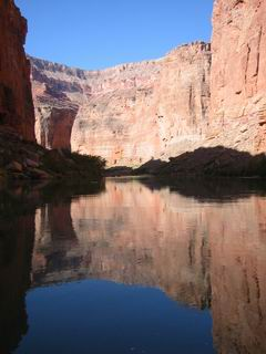 The water is so calm that you can see the canyon through its reflection.